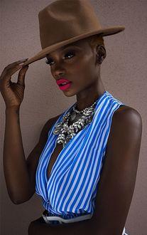 Фото Красивая негритянка в шляпе с яркой помадой на губах и украшением на шее