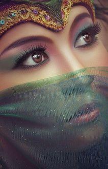 Фото Красивая восточная девушка с закрытым лицом с украшением на голове
