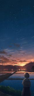 Фото Девочка стоит на дороге перед вечерним городом и небом на закате