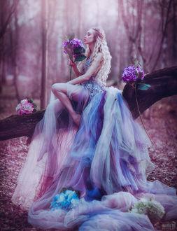 Фото Девушка в платье цвета гортензий с этими цветами сидит на стволе упавшего дерева, фотограф Светлана Беляева