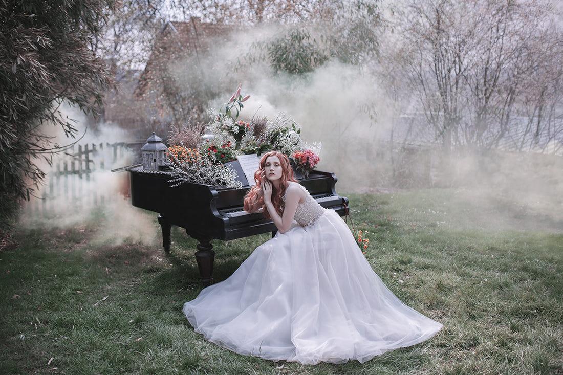 Фото Девушка сидит у рояля, на котором лежат весенние цветы, в саду, окутанным туманом, фотограф Jovana Rikalo