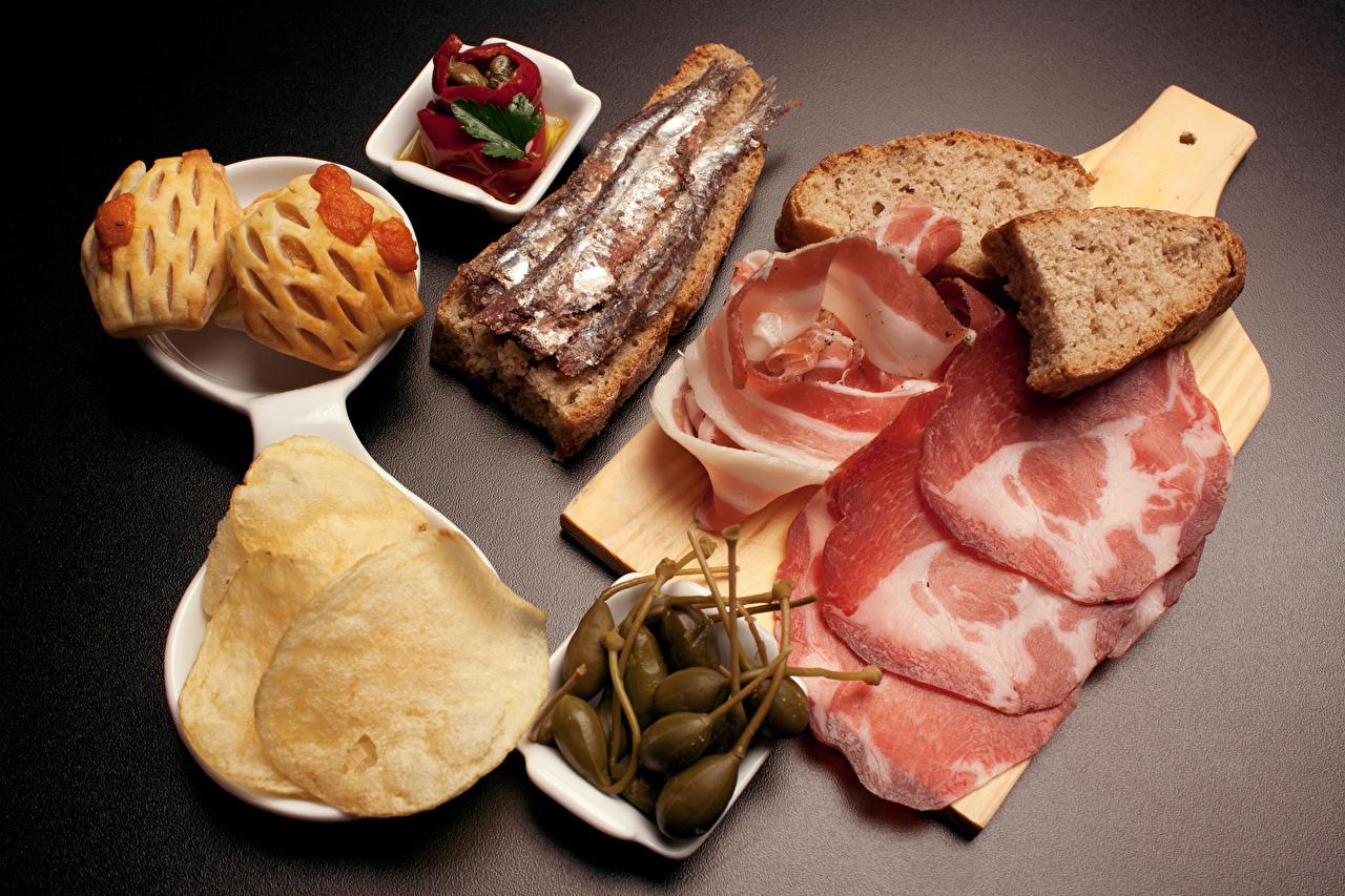 Фото Натюрморт из нарезанной тонкими слайсами пармской ветчины, бутерброда со шпротами, чипсами, каперсами, вялеными помидорами и свежеиспеченной чиабатой