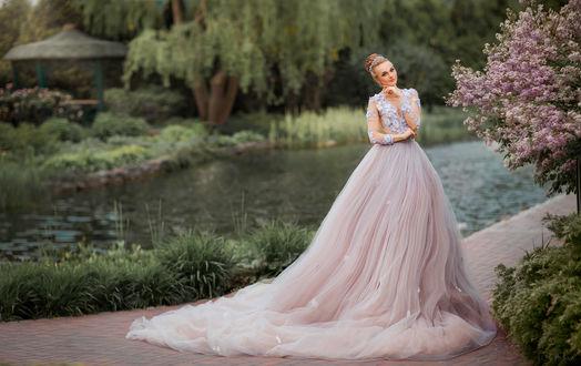 Фото Модель Анна в красивом свадебном платье стоит у цветущего весеннего дерева в парке. Фотограф Ольга Бойко