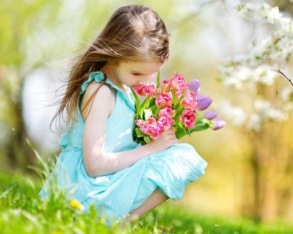 Фото Девочка шатенка в бирюзовом платье сидит на траве с букетом тюльпанов в руке