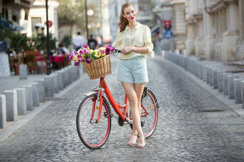 Фото Девушка с велосипедом, на котором прикреплена корзина с весенними цветами, стоит на городской мостовой