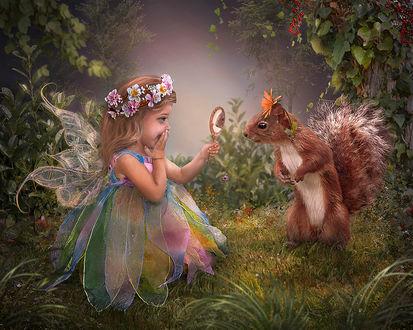 Фото Девочка-ангелочек с крылышками с веночком из цветов, показывает белке ее отражение в зеркале, by Lotta-Lotos