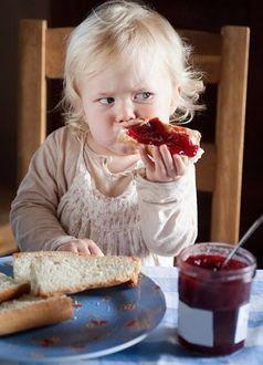 Фото Ребенок кушает бутерброд с вареньем