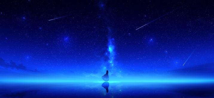 Фото Девушка стоит в воде на фоне ночного неба с млечным путем