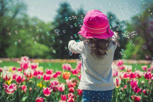 Фото Девочка пускает мыльные пузыри над клумбой с тюльпанами, фотограф Валентин Валков