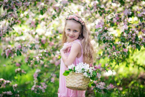 Фото Девочка в венке с корзинкой яблоневых, цветущих ветвей