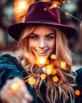 Фото Девушка в шляпе с бенгальским огнем