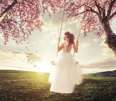 Фото Девушка в белом платье на качелях, между цветущих деревьев, а так-же небо с облаками и летящими птицами. Автор Zsolnai Gergely