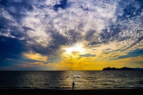 Фото Мужчина стоит у моря под облачным небом