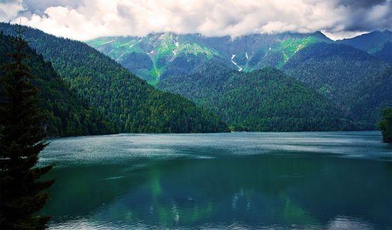 Фото Озеро среди гор покрытых лесом, под небом с облаками