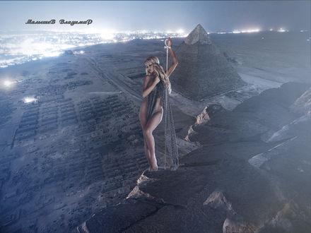 Фото Девушка жрица, стоит на каменной стене и смотрит на пирамиды