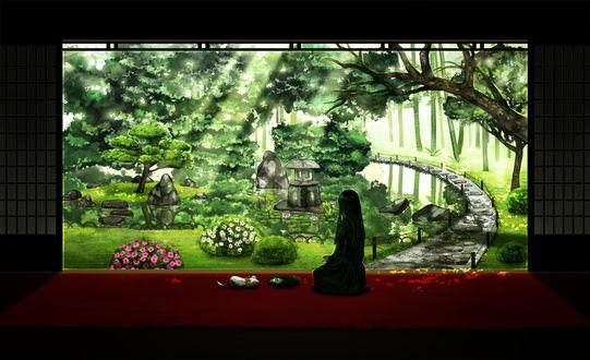 Фото Девушка сидит перед цветущим садом