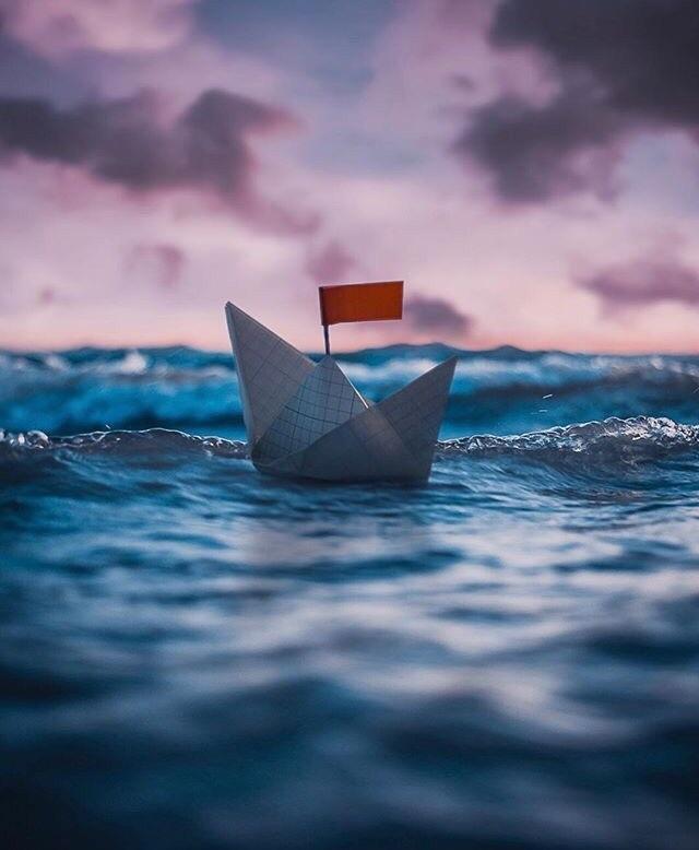 Фото Бумажный кораблик в море на фоне закатного неба