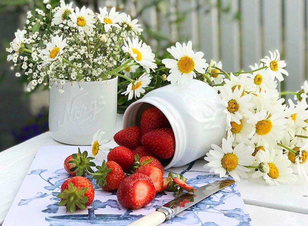 Из фарфоровой вазы высыпалась на стол сочная клубника, рядом лежат ромашки и в вазе стоит букет ромашек