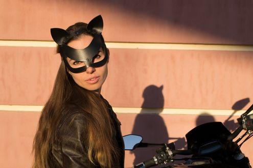 Фото Девушка в кожаной маске кошки на мотоцикле