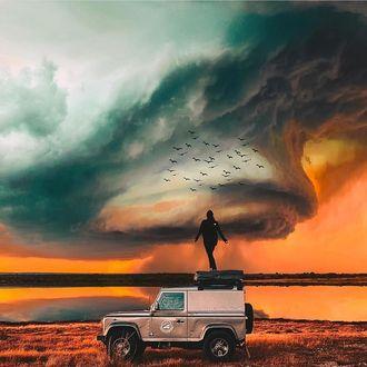Фото Девушка стоит на джипе на фоне огромного облака