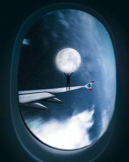 Фото Парень стоит на крыле самолета с луной над руками, вид через иллюминатор, by nasr. j