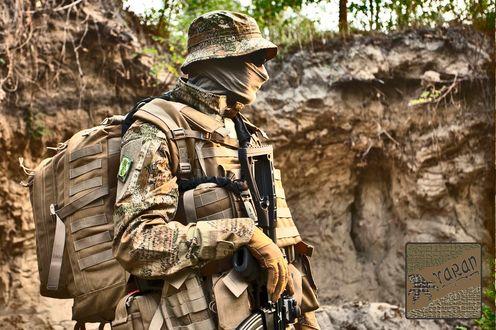 Фото Мужчина в камуфляже Варан с оружием на фоне обрыва из желтой глины