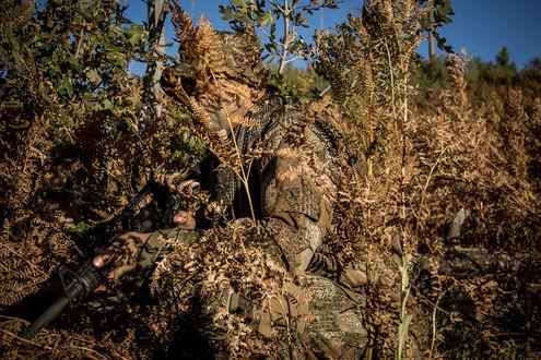 Фото Мужчина в камуфляже Варан с оружием замаскировался среди желто-зеленой растительности