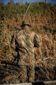 Фото Мужчина в камуфляже Варан стоит спиной на фоне желто-зеленой растительности