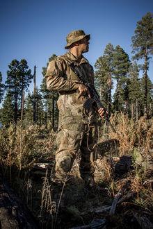 Фото Мужчина в камуфляже Варан с оружием стоит на фоне желто-зеленой растительности