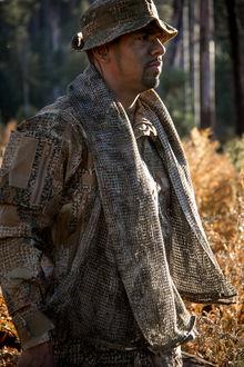 Фото Мужчина в камуфляже Варан стоит на фоне желто-зеленой растительности