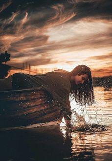 Фото Девушка опустила руку в воду