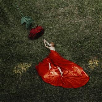 Фото Девушка в красном платье лежит на траве, протянув руки к розе, фотограф Jovana Rikalo