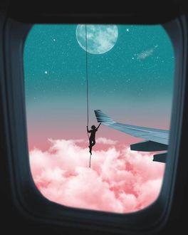 Фото Парень на веревке весит на фоне облаков и дотрагивается до крыла самолета