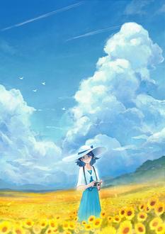 Фото Девушка в шляпе с фотоаппаратом в руках стоит на поле подсолнухов