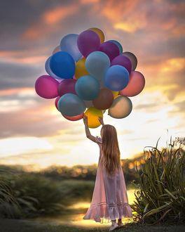 Фото Девочка с воздушными шарами на фоне природы