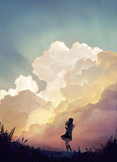 Фото Школьница стоит в траве на фоне облачного неба