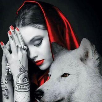 Фото Девушка с закрытыми глазами с тату на руках держит бусы, а рядом с ней белый волк