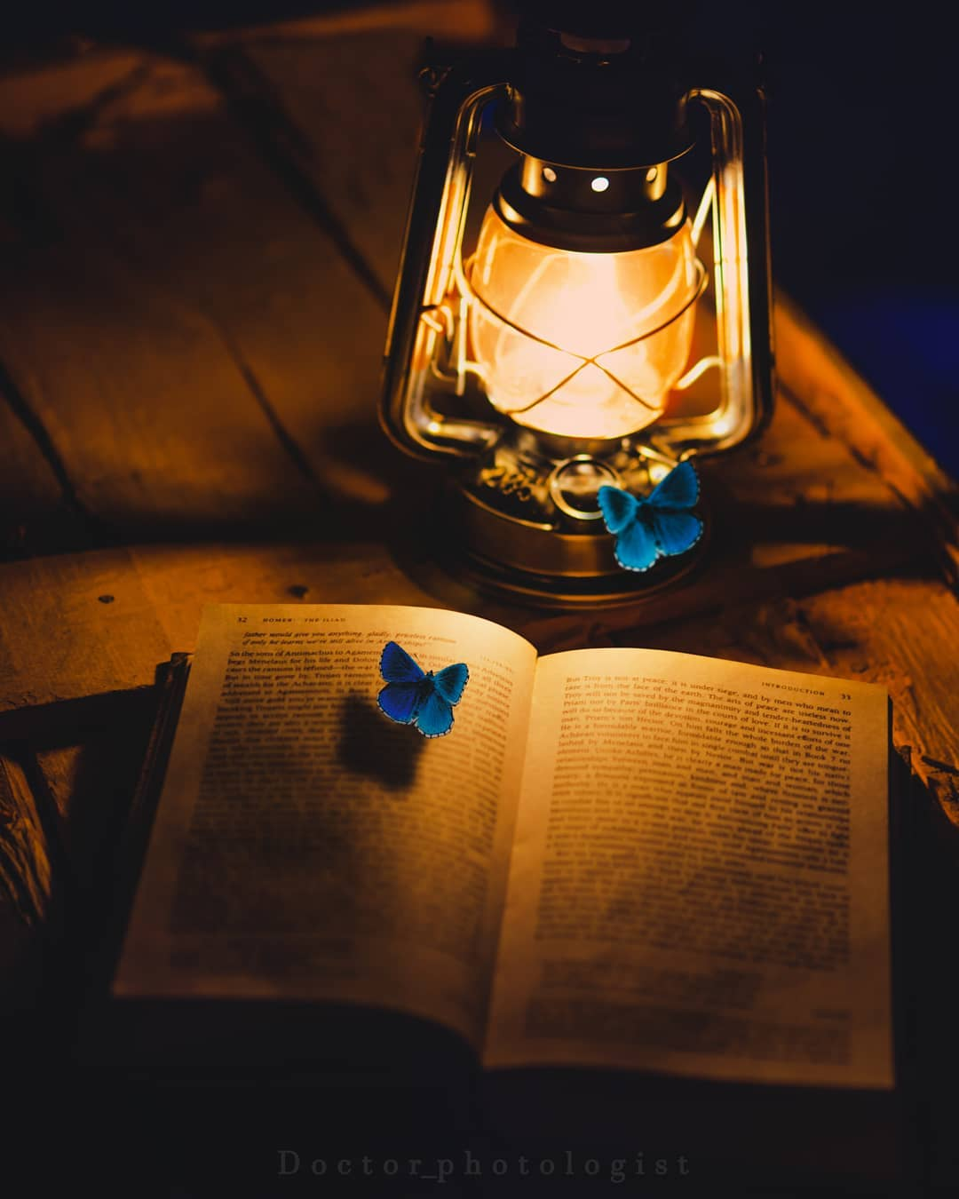 Фото Горящий фонарь стоит рядом с открытой книгой с бабочкой на ней и на нем самом, by hossein mahmoudpour