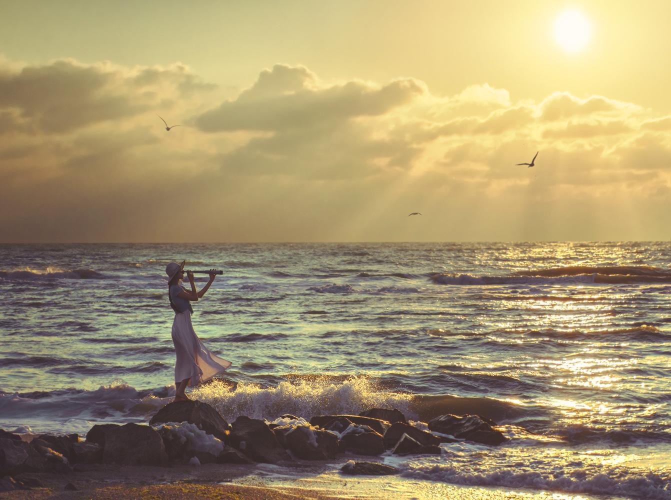Девушка в шляпе с подзорной трубой в руках стоит у моря. Фотограф Давид Д