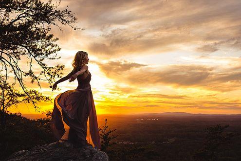 Фото Девушка стоит на камне на фоне неба во время заката. Фотограф Katya Vilchyk