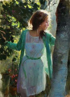 Фото Утонченная девушка одетая в зеленый кардиган с белым платьицем, гуляя по саду мечтательно смотрит по сторонам
