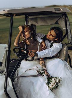 Фото Модель Анастасия Щеглова в белом свадебном платье, с розами в руке, сидит в авто рядом с парнем. Фотограф Viktoria Romanova