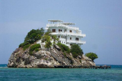Фото Дом на скале в окружении моря