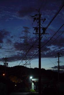 Фото Домик с горящим фонарем под ночным небом с телеграфными столбами