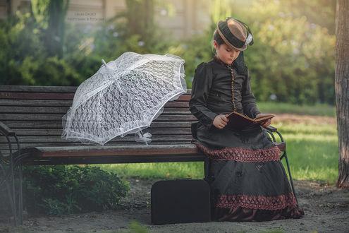 Фото Девочка сидит на скамейки и читает книжку, фотограф Malika Drobot
