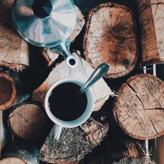 Фото Чашка кофе и кофейник стоят на дровах