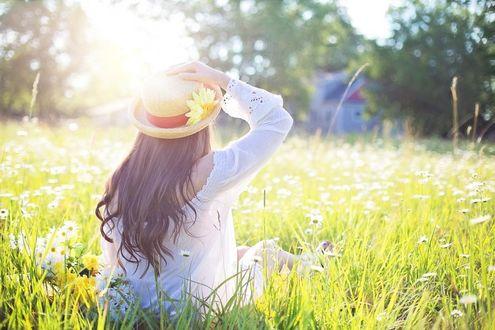 Фото Девушка в шляпе сидит в траве к нам спиной