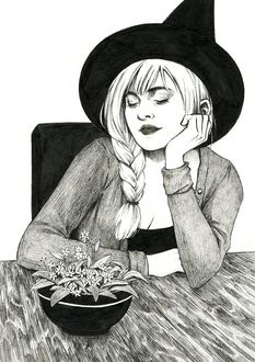 Фото Девушка в ведьминой шляпе сидит за столом перед цветком в горшке