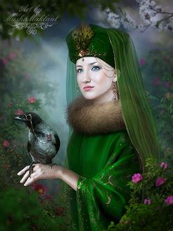 Фото Голубоглазая девушка в зеленом наряде с украшениями стоит под цветущим деревом с вороной на руке. Автор Маша Маклаут