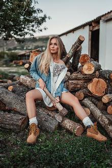 Фото Модель Наталья с топором в руках сидит на бревнах, Фотограф Фрейер Евгений